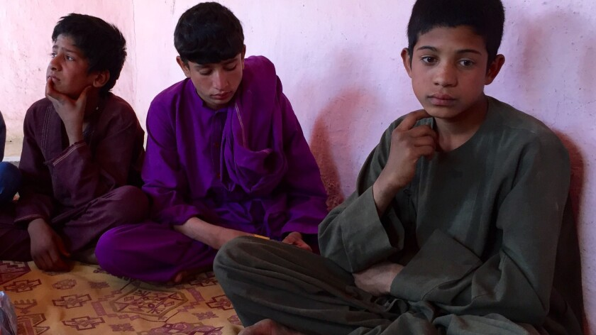 Wakil, 14, right, polishes shoes to help his family make ends meet at a camp for displaced people in Kabul.