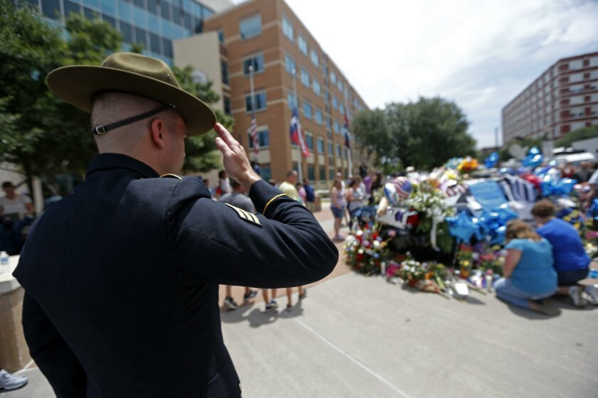 Ret. Army Sgt. Chandler Davis, who served overseas as a combat medic, salutes at a makeshift memorial of police cars in honor of the slain Dallas police officers.