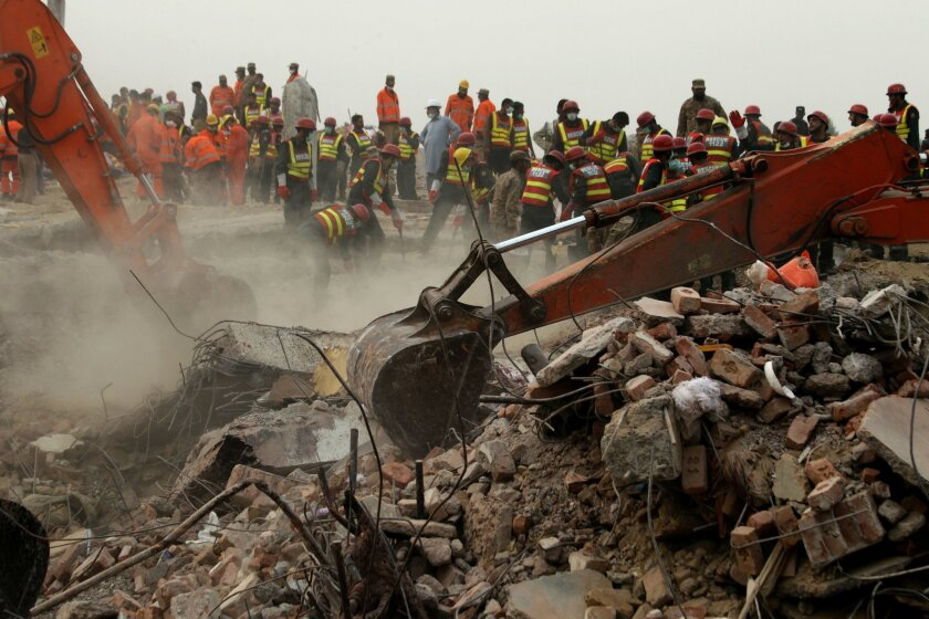 Excavators dig rubble of a collapsed building looking for survivors in Lahore, Pakistan, Friday, Nov. 6, 2015. A spokesman for a Pakistani rescue agency says hopes are starting to fade for finding more survivors in the rubble of a four-story factory which collapsed this week killings dozens of peop