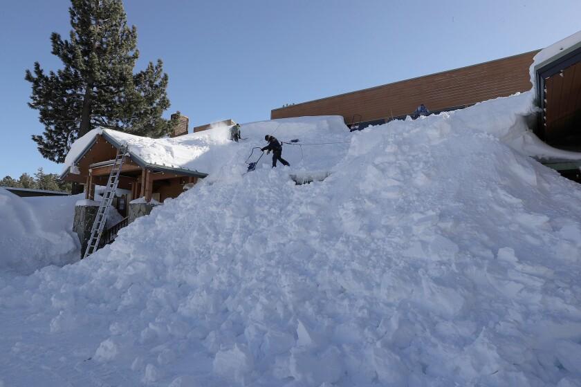 Workers shovel giant snowdrifts off the roof of the Mammoth Luxury Outlets in Mammoth Lakes on Feb. 6 after a blizzard dropped as much as 10 feet of snow.