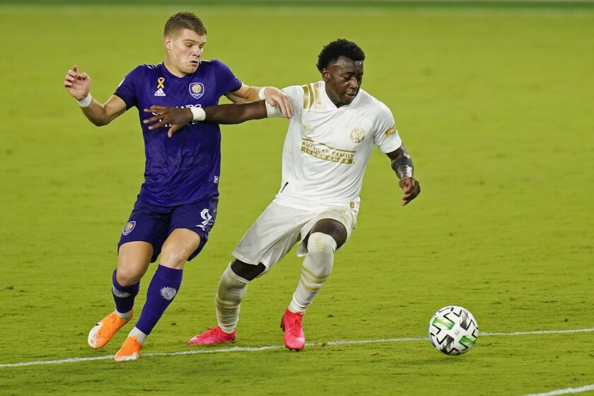 Orlando City's Chris Mueller (9) and Atlanta United's George Bello, right, fight for possession of the ball during the second half of an MLS soccer match, Saturday, Sept. 5, 2020, in Orlando, Fla. (AP Photo/John Raoux)