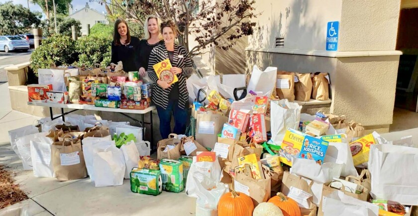"Sharon Anderson, a local realtor, spearheaded a food drive to benefit Angels Outreach, which adopts military families in need and is based out of Calvary Lutheran Church in Solana Beach. Anderson asked a couple colleagues and her husband to join in the effort with hopes they might double the amount they collected last Thanksgiving--which was 300 items. The four of them set out in the community and knocked on more than 750 doors, dropping off donation bags. There was also a donation box at Keller Williams Carmel Valley for local realtors to donate. When the four returned to the neighborhoods to collect the bags of food Anderson saw there was much more than double of last years donations -- 1,900 food items, totaling almost 2,000 pounds of food. "" We are grateful for the overwhelming community support,"" Anderson said. Left to right: Realtors Dana Swanson and Elizabeth Raber with Anderson showing the food they collected. Non-perishable food items will continue to be collected through Dec. 8 at Calvary Lutheran Church, 424 Via De La Valle, and can be dropped off there. Email sharon.anderson@kw.com."
