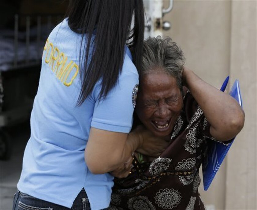 Aniolina Caimol, 63, the grandmother of shooting victim Micaela Caimol, 7, cries after viewing her grand daughter inside a morgue of a private hospital in Kawit township, Cavite province 16 kilometers (10 miles) south of Manila, Philippines Friday Jan. 4, 2013. A man who was apparently intoxicated has fatally shot eight people, including a child who tried to shield herself behind seat cushions, before he was gunned down by police in a town near the Philippine capital, officials said Friday. (AP Photo/Bullit Marquez)
