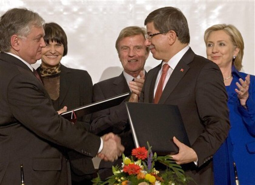 Armenian foreign minister, Edouard Nalbandian, front left, and Turkish foreign minister, Ahmet Davutoglu, front right, shake hands while Swiss foreign minister, Micheline Calmy-Rey, French foreign minister, Bernard Kouchner, and US Secretary of State, Hillary Rodham Clinton, back from left, applaude during the signing ceremony of the protocols and statements between Armenia and Turkey, at the University of Zurich in Zurich, Switzerland, Saturday, Oct. 10, 2009. Turkey and Armenia are poised to normalise relations as part of a landmark agreement brokered by Switzerland and strongly backed by the United States. (AP Photo/KeystonePartick B. Kraemer,Pool)