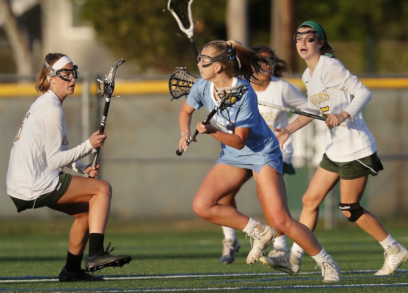 Corona del Mar High's Joslyn Simaan, center, carries the ball against Edison during the first half i