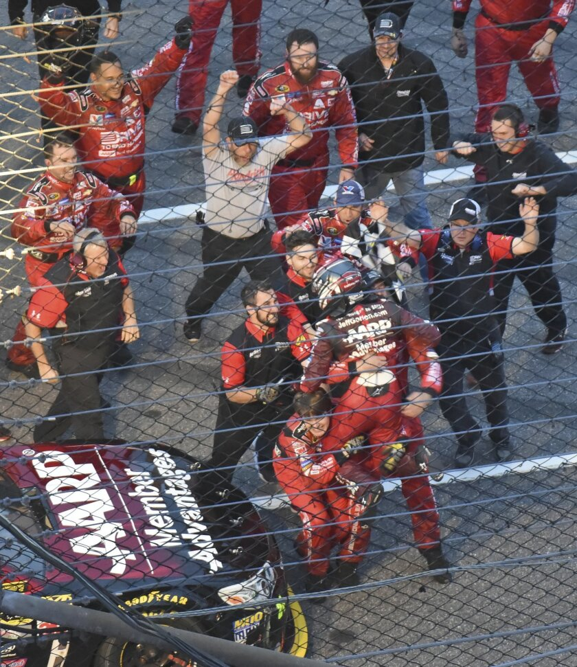 Jeff Gordon (wearing helmet) celebrates with his team after winning the NASCAR Sprint Cup Series auto race a Martinsville Speedway in Martinsville, Va., Sunday, Nov. 1, 2015. (AP Photo/Don Petersen)