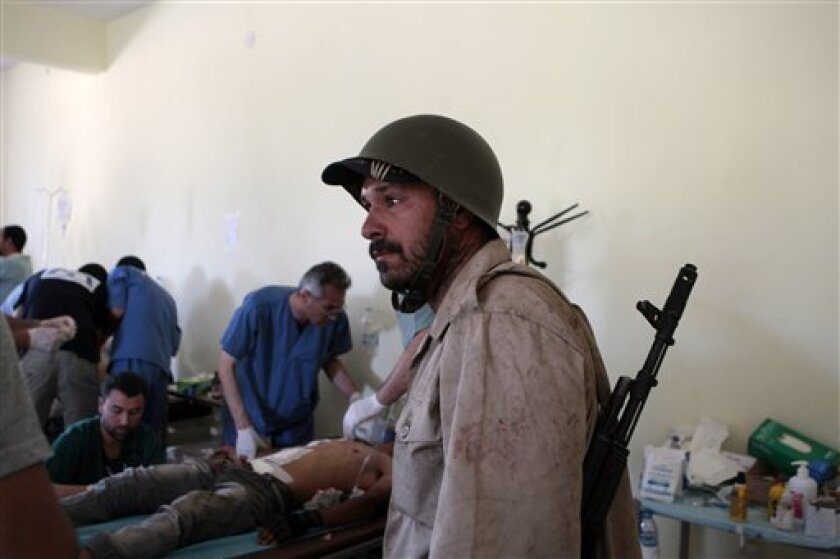 A Libyan rebel fighter arrives at a hospital as others receive treatment in Misrata, Libya, Friday, June 10, 2011. Libyan government forces pounded the outskirts of the rebel-held city of Misrata on Friday, killing at least 22 people, a hospital physician said. (AP Photo/Luis Hidalgo)