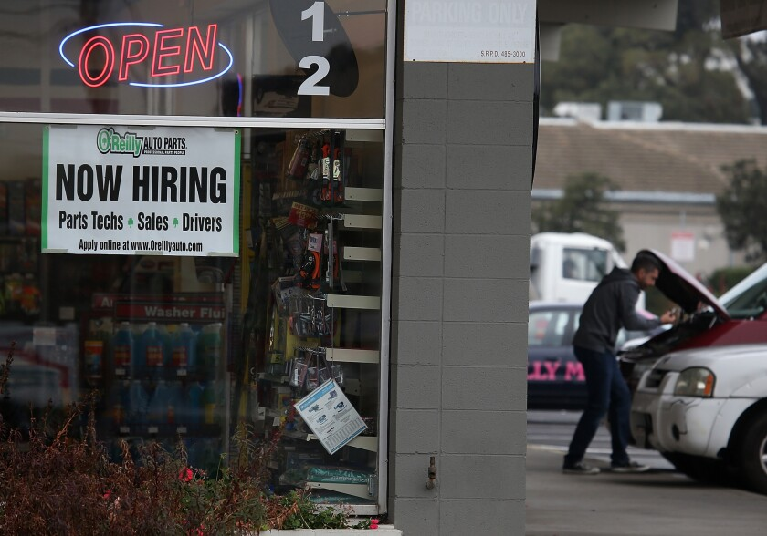 """A """"now hiring"""" sign is posted in window of an O'Reilly auto parts store in San Rafael, Calif., last month."""
