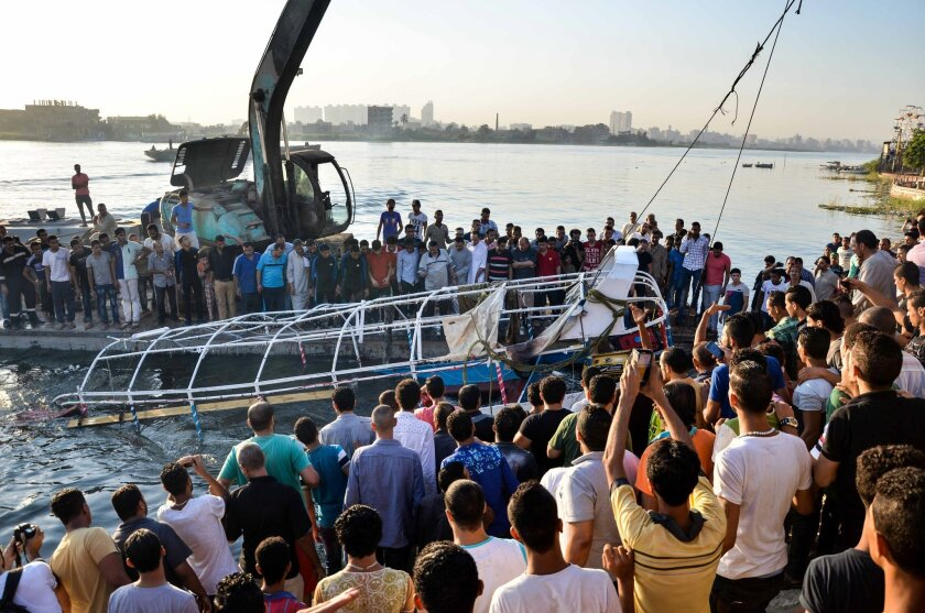 Egyptians look at the passenger boat that sunk in the river Nile in Giza, south of Cairo, Egypt, Thursday, July 23, 2015. Egypt's Interior ministry says more than a dozen civilians have drowned when the passenger boat traveling down the Nile near Cairo collided with a scow, causing the boat to capsize. (AP Photo/Samer Abdullah)