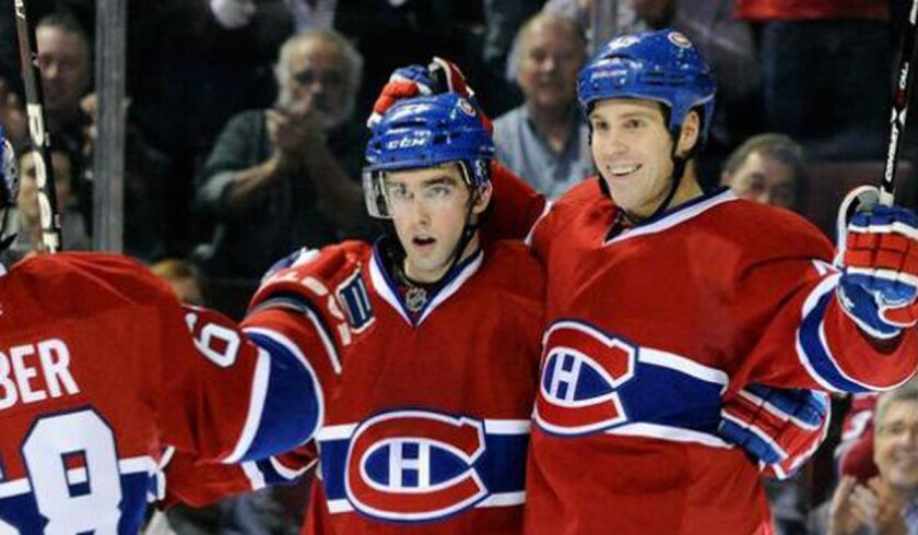 Louis Leblanc, center, celebrates a goal with Canadiens teammates including Michael Blunden, right.
