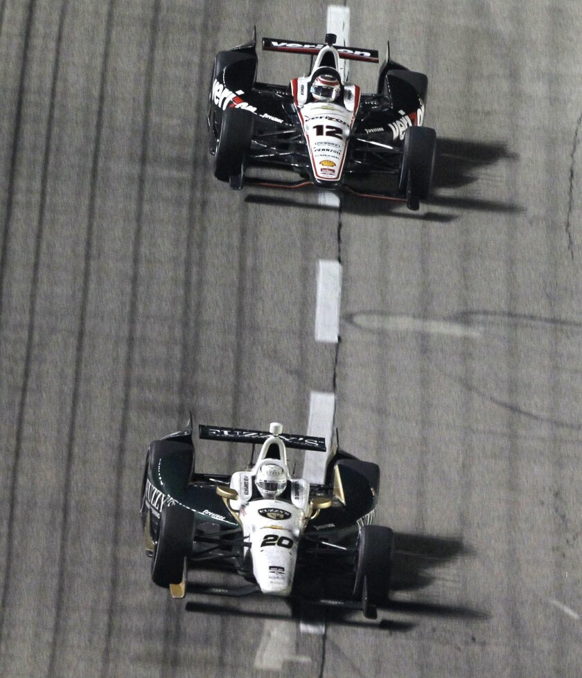 Ed Carpenter (20) drives in front of Will Power (12), of Australia, during an IndyCar auto race at Texas Motor Speedway in Fort Worth, Texas, Saturday, June 7, 2014. Carpenter went on to win the rave. (AP Photo/Ralph Lauer)