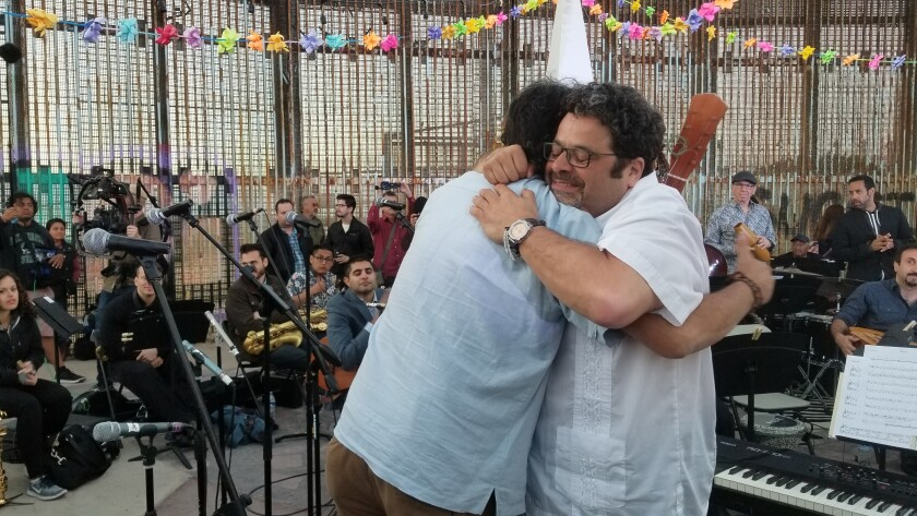 """Arturo O'Farrill (right) and Jorge Castillo hug after performing at a May 2018 concert on the Tijuana side of the U.S.-Mexico border that was led by four-time Grammy Award winner O'Farrill. That concert, and another held simultaneously on both sides of the border, has resulted in a documentary film, a book and a two-CD album that will be the basis for the March 14 """"Fandango at the Wall"""" concert at San Diego's Copley Symphony Hall."""