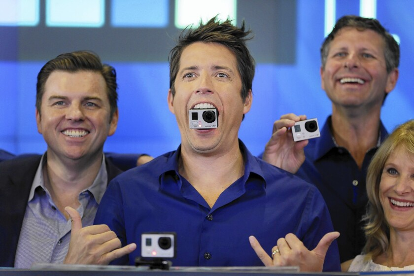 GoPro CEO Nick Woodman holds a GoPro camera in his mouth as he and others celebrate his company's IPO in New York on Thursday.