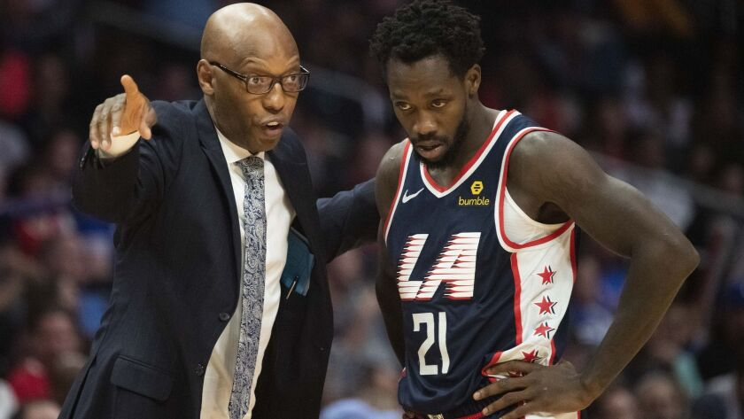 Clippers assistant coach Sam Cassell talks to guard Patrick Beverley during a game against the Denver Nuggets on Dec. 22.