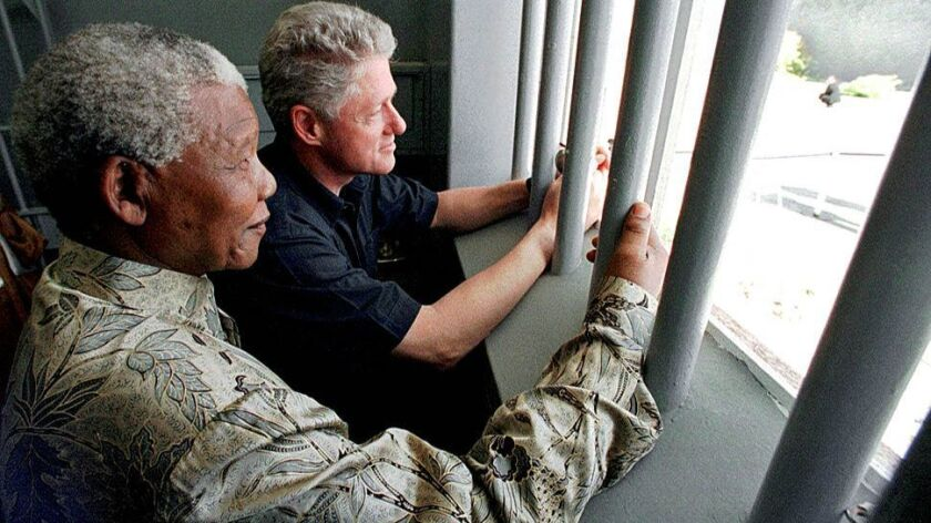 Presidents Mandela and Clinton look out from a cell on Robben Island in Cape Town's Table Bay in 1998. Mandela spent 18 of his 27 years in this prison cell during apartheid.