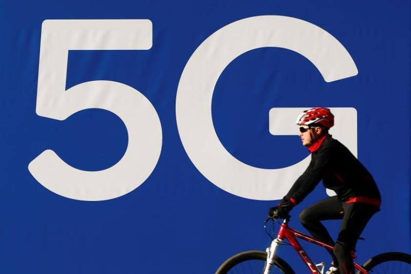 En la imagen del pasado día 23, un ciclista pasa ante un cartel de redes 5G instalado en las inmediaciones de la Fira de Barcelona. EFE