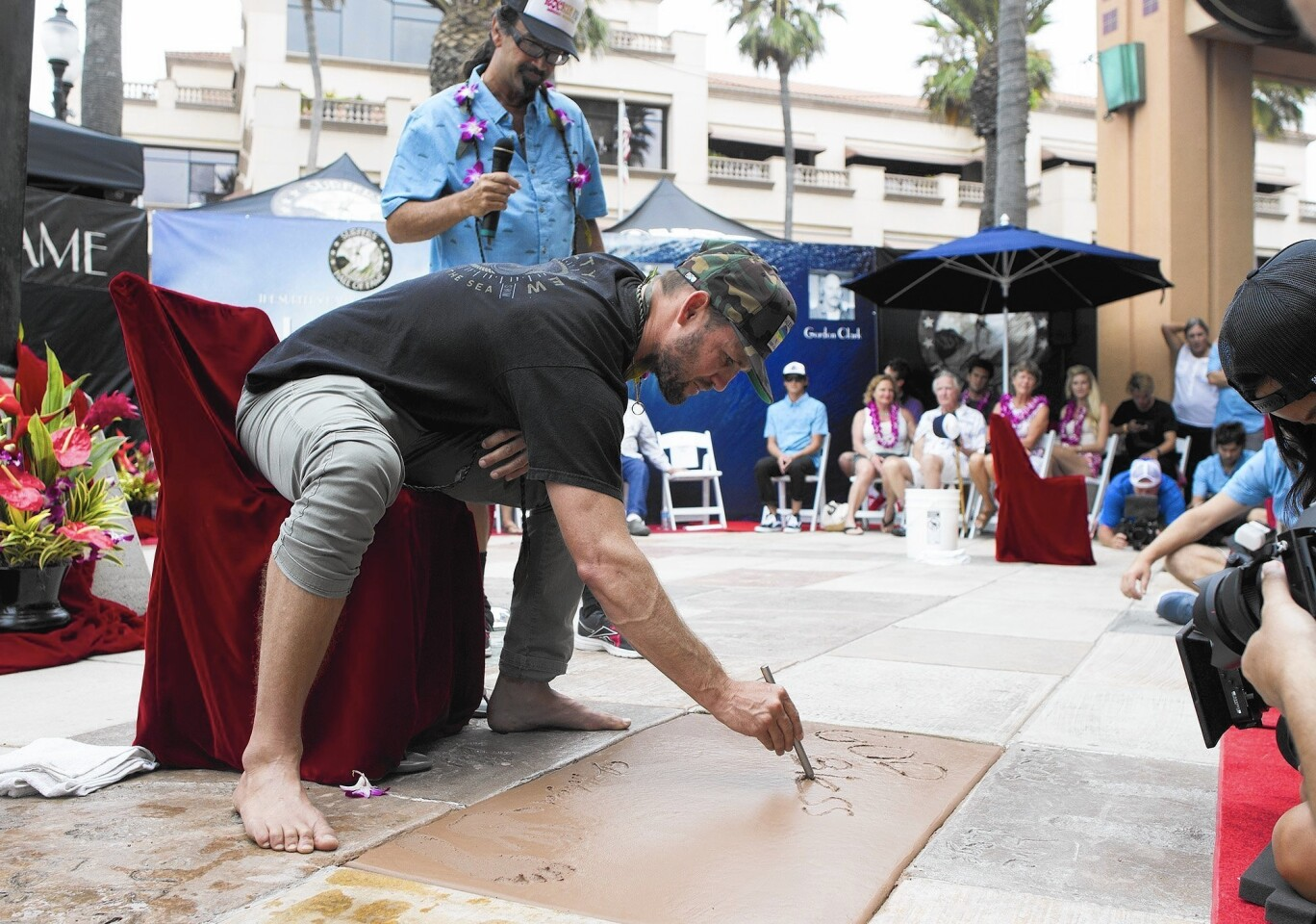 """Surfer Clifton James """"C.J."""" Hobgood, a new member of the Surfers' Hall of Fame, writes the words """"God bless"""" on a cement slab during Friday's induction ceremony in Huntington Beach."""
