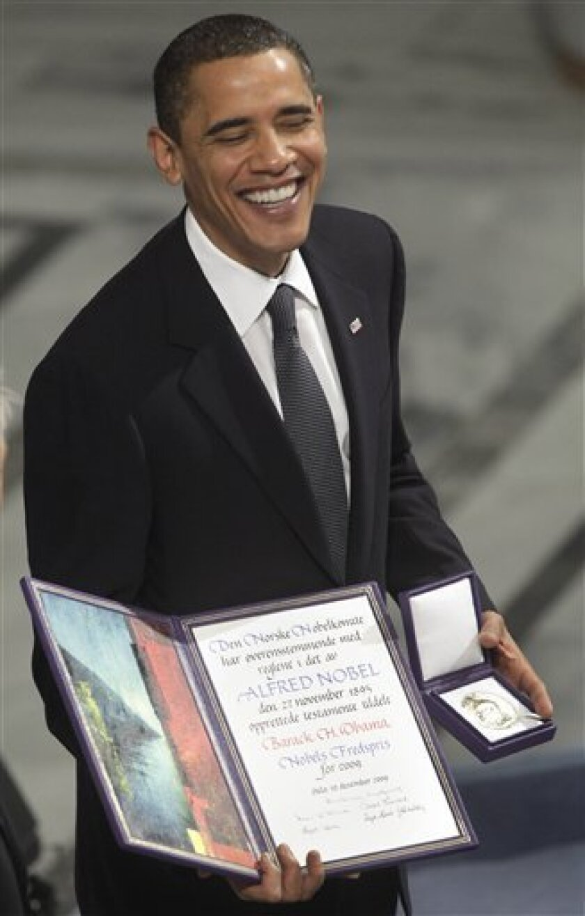 President and Nobel Peace Prize laureate Barack Obama poses with his medal and diploma at the Nobel Peace Prize ceremony at City Hall in Oslo, Thursday, Dec. 10, 2009. (AP Photo/Odd Andersen)