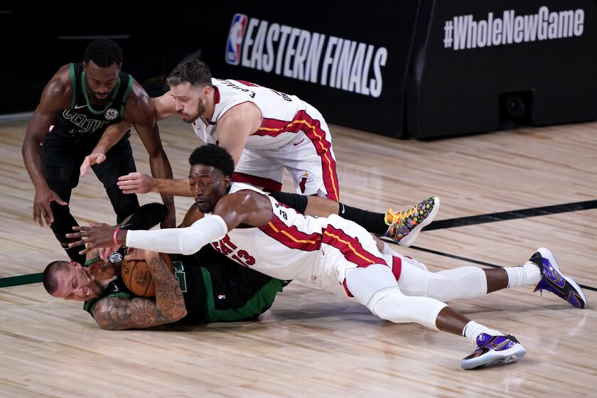 Boston's Kemba Walker and Daniel Theis attempt to gain control of a loose ball against Miami's Goran Dragic and Bam Adebayo.