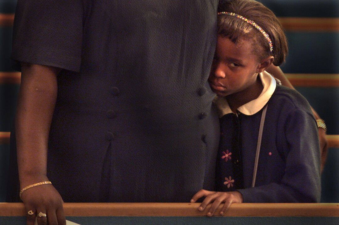 A young girl stands next to her grandmother in church