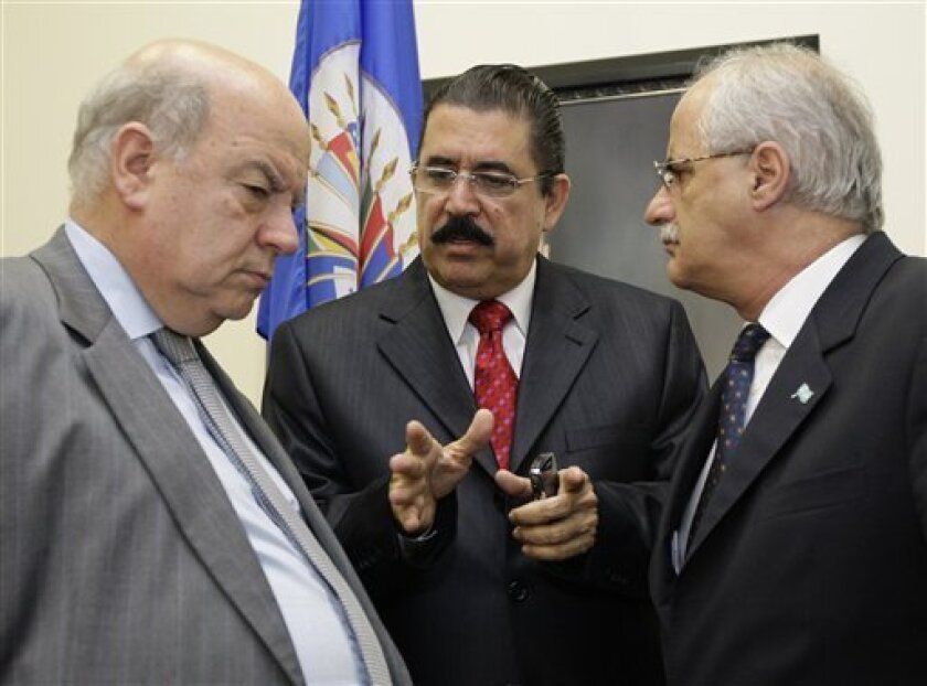 "Ousted Honduran president Manuel Zelaya, center, talks with Jose Miguel Insulza, left, the secretary general of the OAS, and Jorge Taiana, president of the general assembly from Argentina, after a press conference after a meeting of the Organization of American States in Washington early Wednesday, July 1, 2009. A defiant Roberto Micheletti said in an interview with The Associated Press late Tuesday that ""no one can make me resign,"" defying the United Nations, the Organization of American States, the Obama administration and other leaders that have condemned the military coup that ousted President Manuel Zelaya. (AP Photo/Alex Brandon)"
