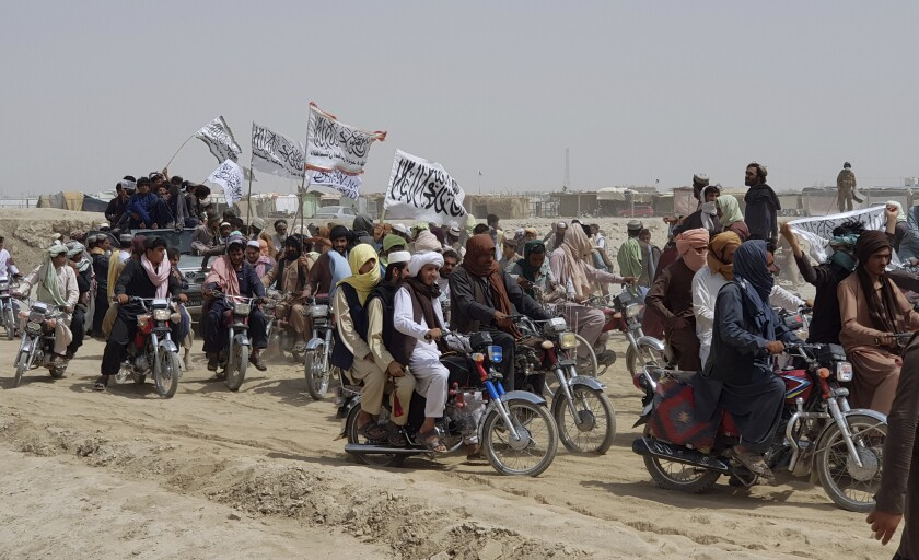 A truck carrying men joins many others riding on motorcycles, some carrying white flags with Arabic script