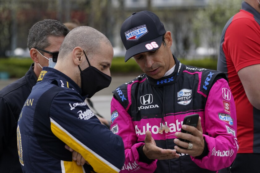 Tony Kanaan, of Brazil, left foreground, talks with Helio Castroneves, of Brazil, before testing at the Indianapolis Motor Speedway, Thursday, April 8, 2021, in Indianapolis. (AP Photo/Darron Cummings)