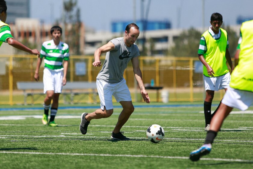 U.S. soccer legend Landon Donovan plays with young players at a local coaching camp.