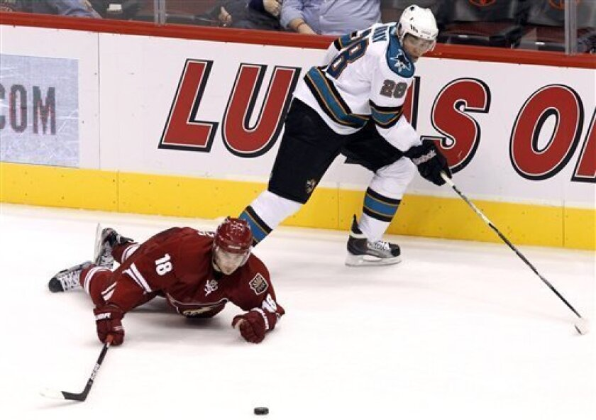 Phoenix Coyotes' Patrick O'Sullivan (18) reaches for the puck after being tripped up by San Jose Sharks' Andrew Murray (28) during the third period in a preseason NHL hockey game, Saturday, Oct. 1, 2011, in Glendale, Ariz. The Coyotes defeated the Sharks 3-1. (AP Photo/Ross D. Franklin)