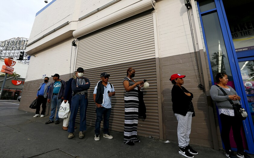 In April, people line up outside a store in Westlake, which has one of Los Angeles County's highest coronavirus infection rates and leads the nation in levels of overcrowded housing.