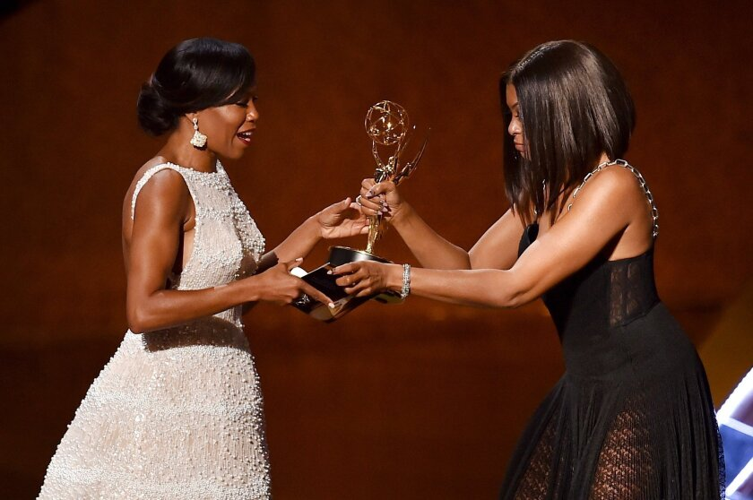 Actress Regina King, left, accepts the Emmy for outstanding supporting actress in a limited series or movie award for 'American Crime' from actress Taraji P. Henson.