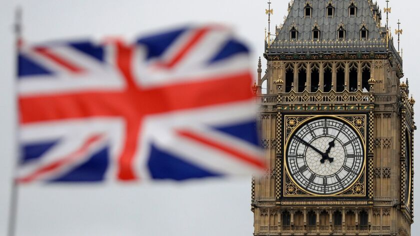 British Union flag waves in front of the Elizabeth Tower at Houses of Parliament containing the bell