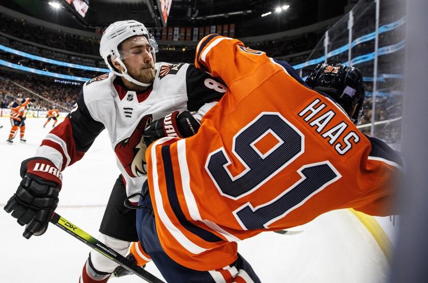 Arizona Coyotes ' Jordan Oesterle (82) checks Edmonton Oilers' Gaetan Haas (91) during second-period NHL hockey game action in Edmonton, Alberta, Monday, Nov. 4, 2019. (Jason Franson/The Canadian Press via AP)