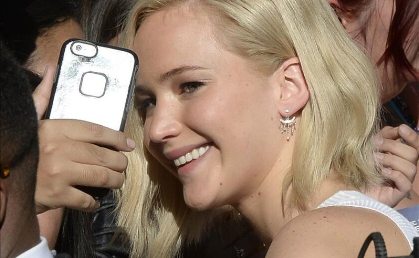"""La actriz Jennifer Lawrence (d) posa con sus seguidores durante la presentación de la película """"Mockingjay - Part 2"""", en Los Ángeles."""