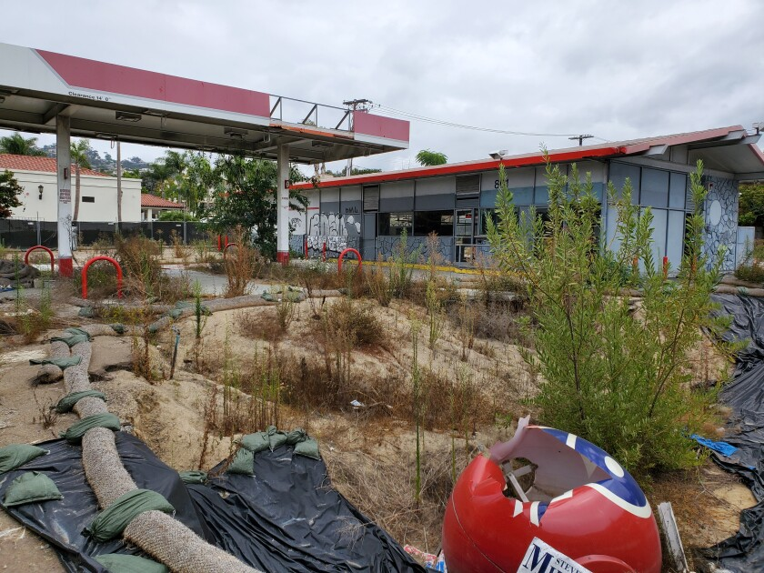 The former 76 gas station at 801 Pearl St. in La Jolla is partially demolished and overgrown with weeds.