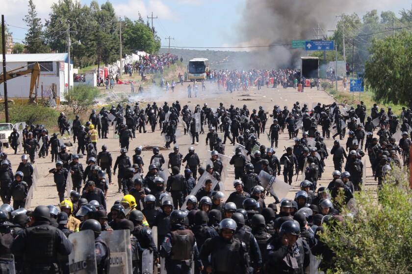 En esta imagen del domingo 19 de junio de 2016, policía antimotines se ve obligada a retroceder en un choque con una protesta de maestros, que bloquearon una autopista federal en el estado de Oaxaca cerca de la localidad de Nochixtlán, México. (AP Foto/Luis Alberto Cruz Hernandez)