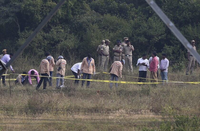 Indian policemen watch the forensic experts investigate at the site where four men suspected of raping and killing a woman were killed in Shadnagar some 50 kilometers or 31 miles from Hyderabad, India, Friday, Dec. 6, 2019. Indian police on Friday fatally shot and killed four men suspected of raping and killing a woman in southern India, leading some to celebrate their deaths as justice in a case that has sparked protests across the country. (AP Photo/Mahesh Kumar A.)