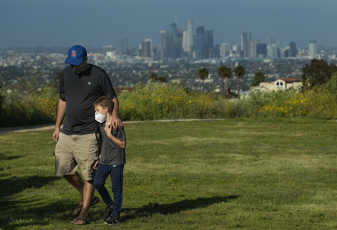 Lee Bloom, 39, of Los Angeles and his son Evan, 7 wear protective masks against the coronavirus during a visit to Kenneth Hahn State Recreation Area in Los Angeles.