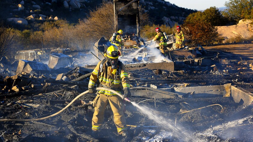 Fire fighters mop up after a fire destroyed a residential home on Salida del Sol in the community of Mount Woodson in Ramona.
