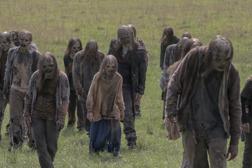 """Zombies in a field in a scene from """"The Walking Dead."""""""