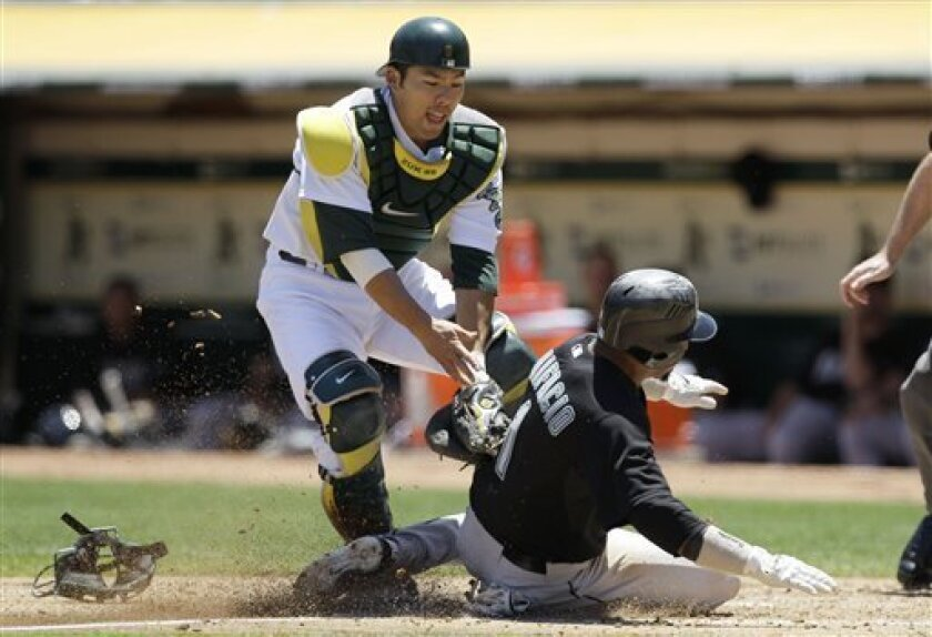 Florida Marlins' Emilio Bonifacio, right, is tagged out on an attempt to score by Oakland Athletics catcher Kurt Suzuki during the third inning of a baseball game, Thursday, June 30, 2011, in Oakland, Calif. (AP Photo/Jeff Chiu)
