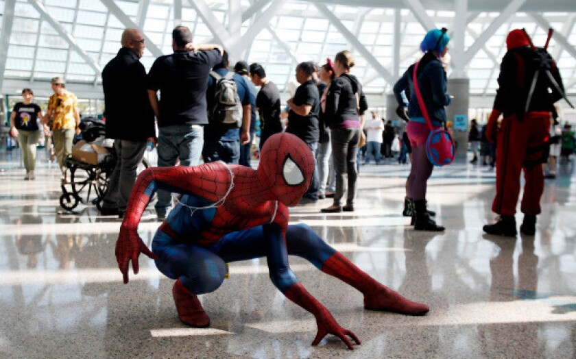A person dressed as Spider-Man poses in a crowd
