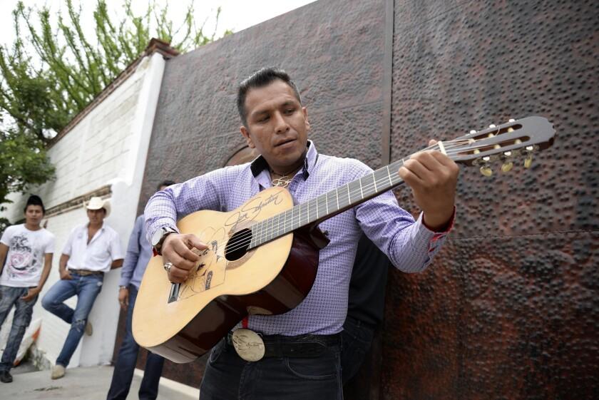 Domingo David, un admirador de Joan Sebastian, toca la guitarra afuera de la casa del cantante mexicano en Teacalco, México, el martes 14 de julio del 2015. Joan Sebastian murió el lunes tras una larga lucha con el cáncer. Tenía 64 años. (AP Foto/Tony Rivera)