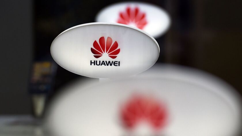 Signs for telecom equipment maker Huawei are displayed in a store selling mobile phones in Beijing. Facebook says Huawei was among four Chinese device makers with which it had a data-sharing agreement.