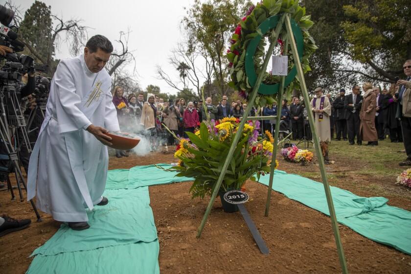 BOYLE HEIGHTS, CALIF. -- WEDNESDAY, DECEMBER 5, 2018: Chaplain Deacon Orlando Rubio blesses the grav
