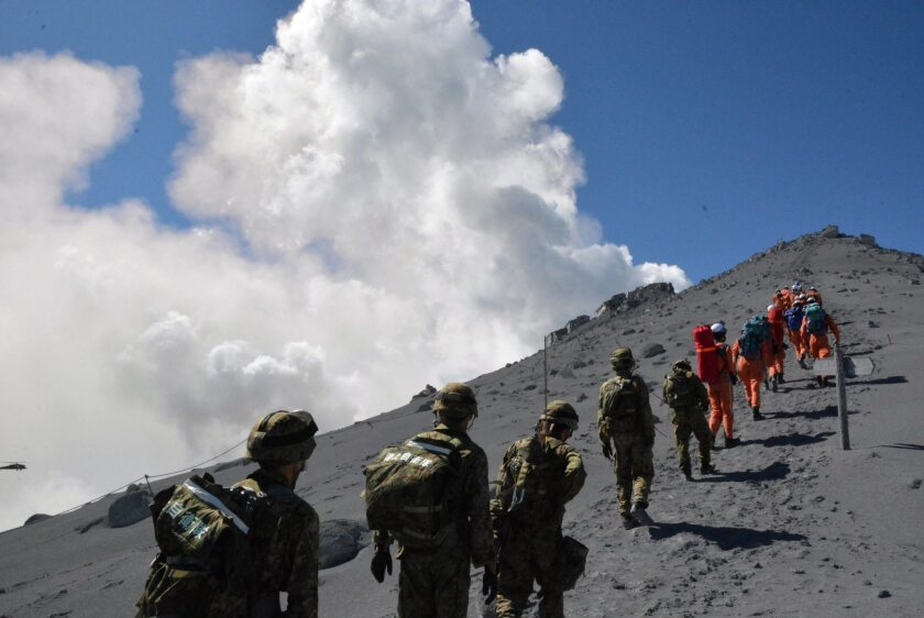 A picture released on Sept. 28 by Japan's Defense Ministry shows Japanese Self-Defense Force members and firefighters during a rescue operation on Mt. Ontake in central Japan.