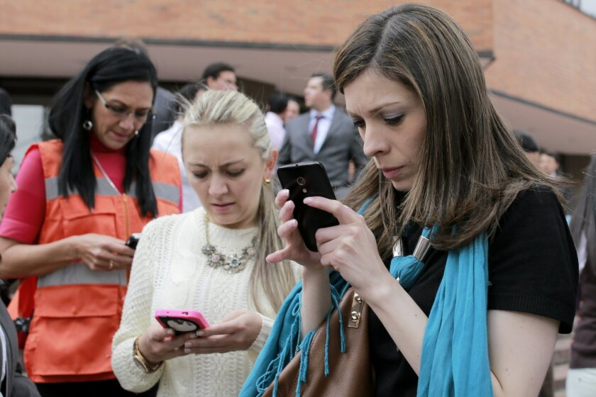 Women use their smart phones after the building where they work in Bogota was evacuated due to an earthquake that shook eastern Colombia causing buildings to sway in the capital Tuesday, March 10, 2015. The quake had a magnitude of 6.2 and was centered near the city of Bucaramanga, about 175 miles
