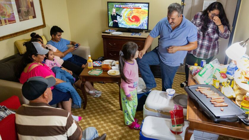The Ramos family prepares dinner and watches the weather forecast as they wait out Hurricane Florence at the Country Inn & Suites in Wilmington, N.C.