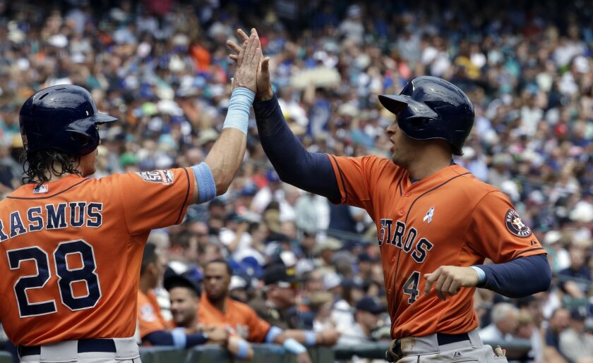 Houston Astros' George Springer, right, is congratulated by teammate Colby Rasmus (28) after scoring against the Seattle Mariners in the first inning of a baseball game Sunday, June 21, 2015, in Seattle. (AP Photo/Elaine Thompson)