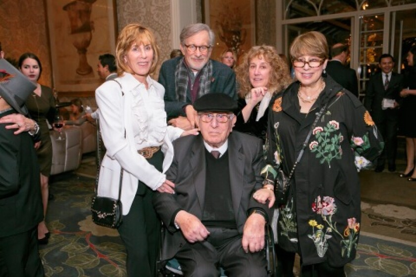 Arnold Spielberg sits in a wheelchair while posing for a photo with his family